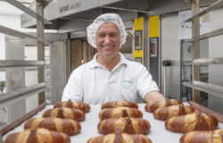 Man with cap and croissants on a baking tray